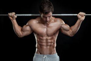 גבר שרירי עם מוט משקולות על הכתפיים